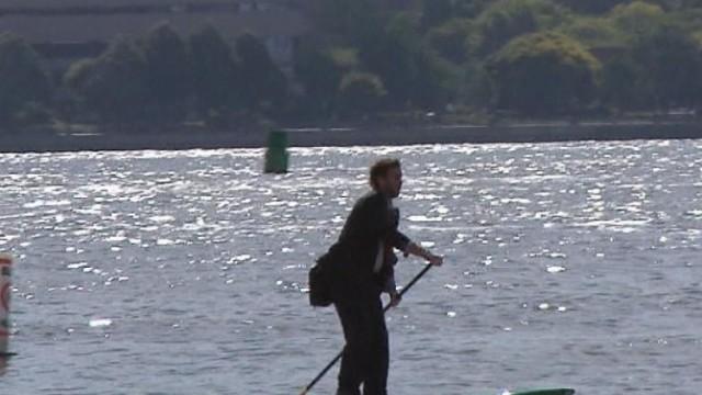 西裝男帶衝浪板划槳渡河上班